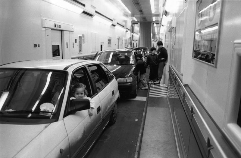 Autos stehen in einer Schlange, im ersten Auto sitzt ein kleines Mädchen am Steuer.