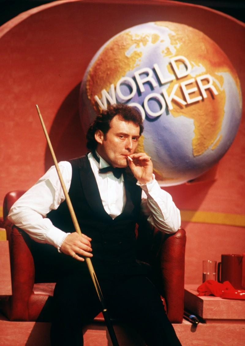 Ein Mann im Anzug hält einen Billard-Stab und raucht eine Zigarette