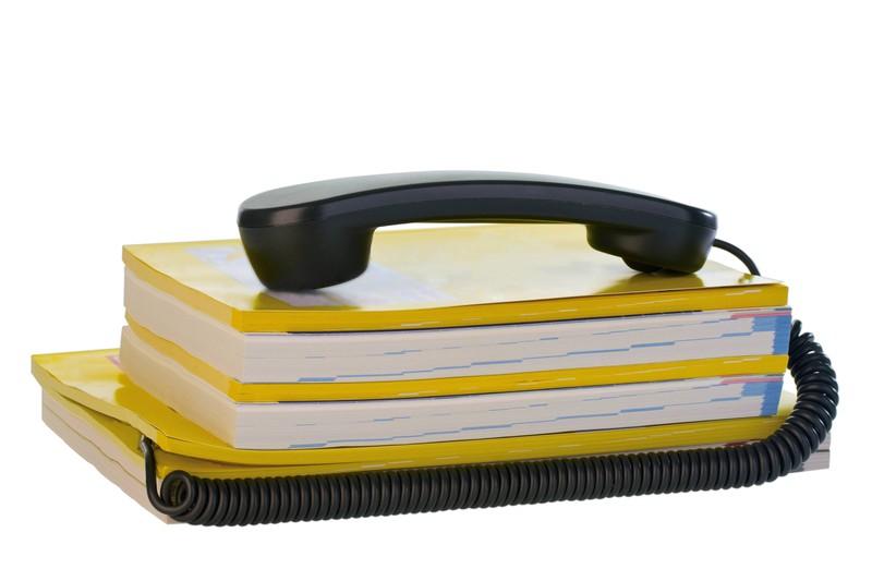 Ein Telefonhörer liegt auf einem Stapel gelber Telefonbücher