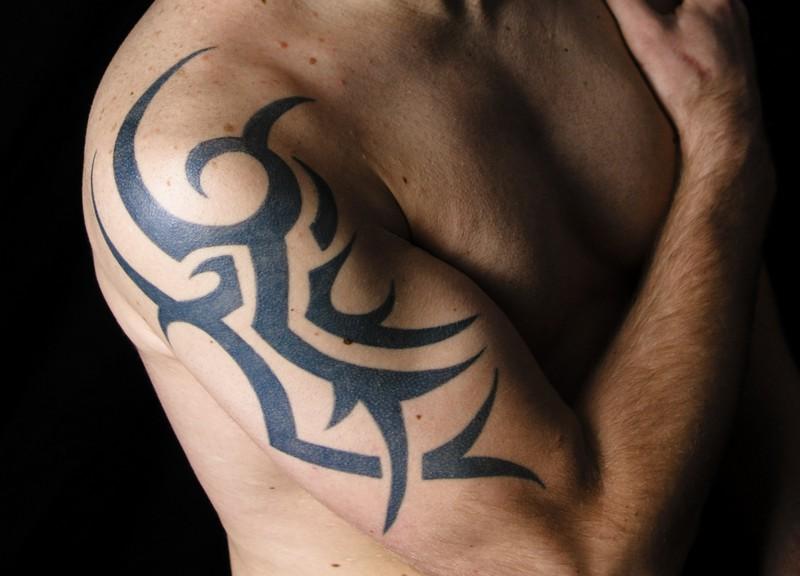 Zu sehen ist ein Arm, auf dem sich ein Tribal-Tattoo befindet