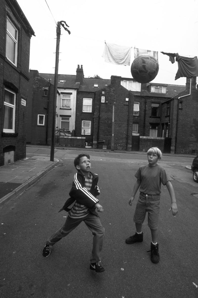 Zwei Jungen spielen Fußball auf der Straße
