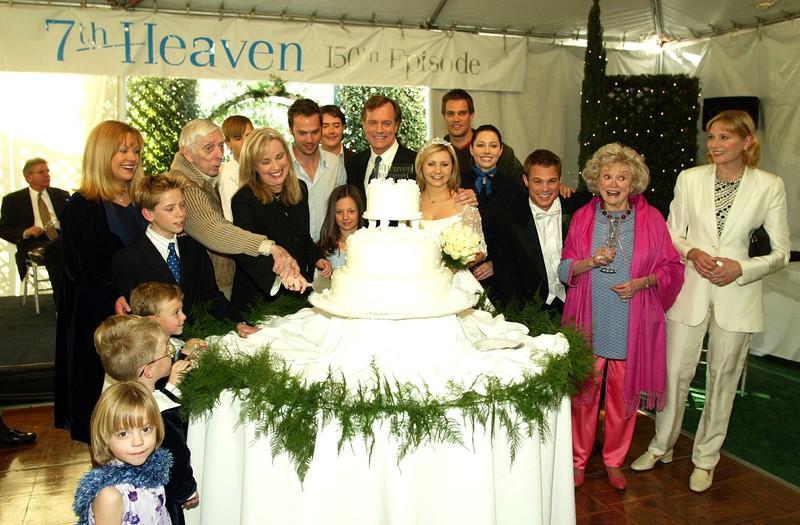 """Der Cast von ,,Eine himmlische Familie"""" steht um einen Kuchen versammelt"""