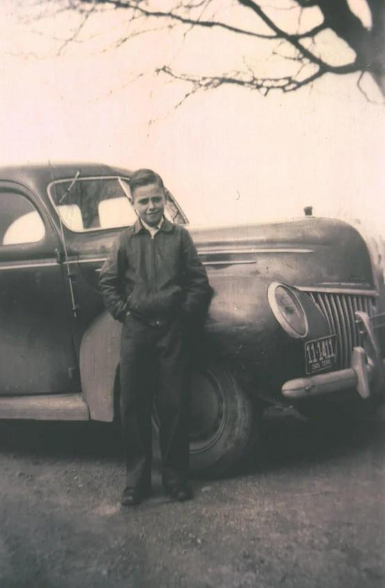 Ein Junge steht stolz vor seinem alten Ford