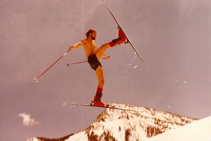 Ein junger Mann führt beim Skifahren einen spektakulären Sprung aus