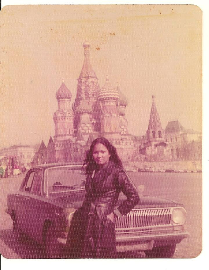 Eine junge Frau im Trenchcoat vor einem Auto in Moskau