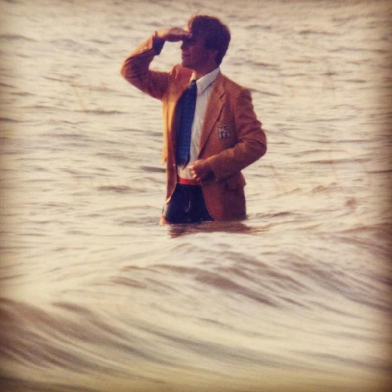 Ungewöhnliche Pose: Ein junger Mann im Anzug steht im Wasser