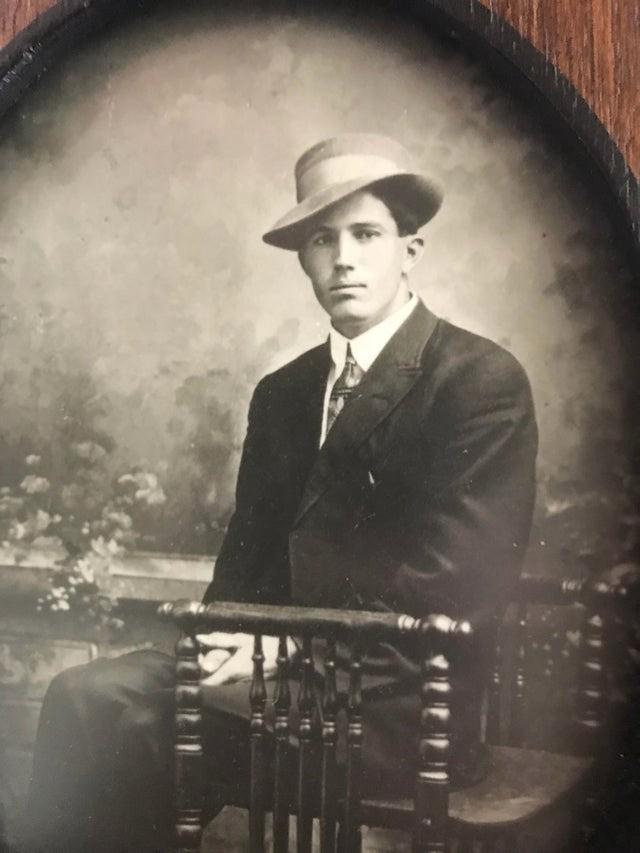 Ein Mann sitzt vor einer Fotokulisse, dabei erinnert er stark an einen Hollywood-Schauspieler.