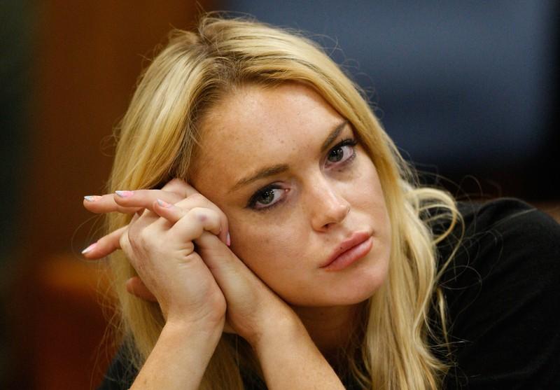 Man sieht Lindsay Lohan und dass sie traurig aussieht, weil sie unter Drogen- und Alkoholeinfluss stand und eine Haftstrafe antreten musste
