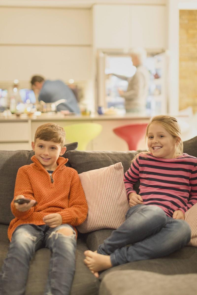 Man sieht Kinder, die im Fernseher gerade die Abenteuer ihrer Disney-Figuren verfolgen