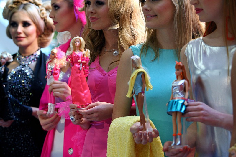 Fünf Frauen halten fünf Barbie Puppen in den Händen
