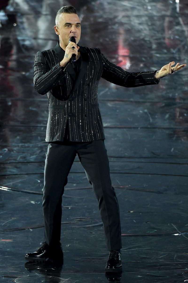 Robbie Williams 2019 auf einer Bühne im Anzug