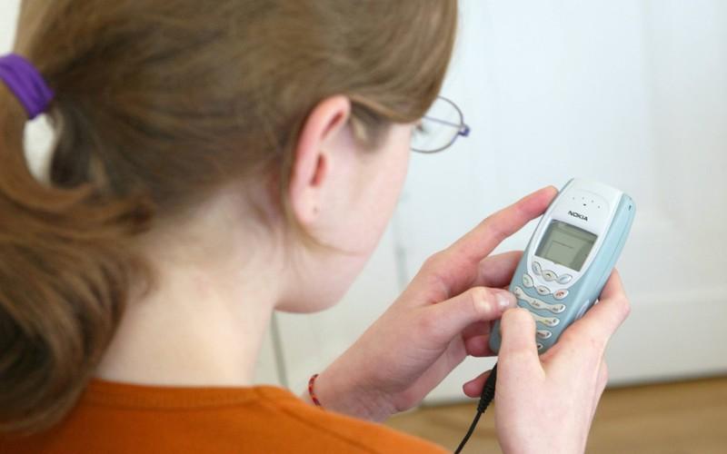 """Ein Mädchen spielt mit einem alten Nokia das Spiel """"Snake"""", was typisch für 90er und 2000er ist."""
