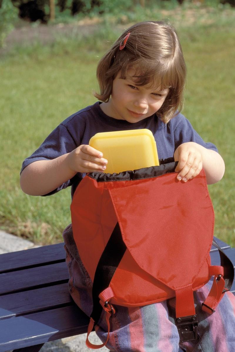 Die Grundschülerin holt ihre Brotbox aus der Schultasche.