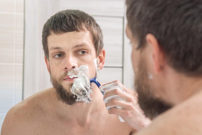 Ein Mann rasiert sich seinen Bart ab