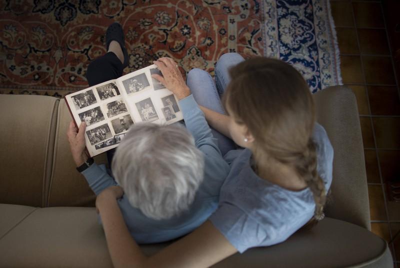Eine alte Frau betrachtet Fotos von früher